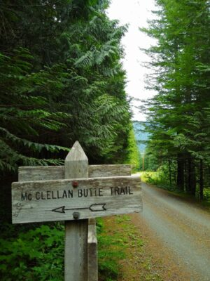 A gravel road through the forest. A wooden sign beside the road reads McClellan Butte trail with an arrow