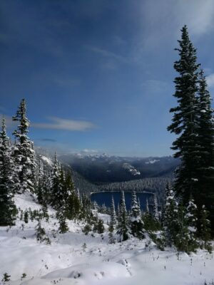 A distant blue lake is seen below and surrounded by snow covered evergreen trees against a blue sky