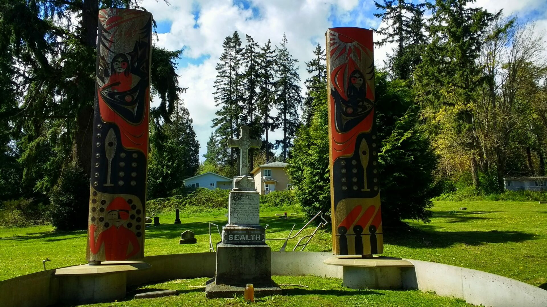 Two poles with carvings in red and black are next to a high stone gravestone which says Sealth and has a white cross on top. It is surrounded by a small cemetery and a few houses in the distance and evergreen trees