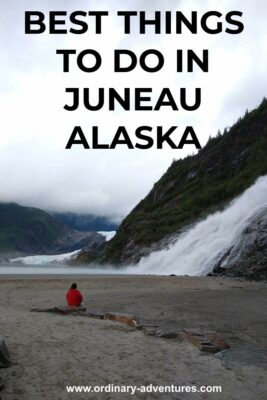 A person in a red rainjacket sits on a rock in a sandy plain. In front of the person is a roaring waterfall over a rocky mountainside. In the distance a glacier and a lake can be seen. Text reads: Best things to do in Juneau Alaska