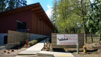 A large wooden building surrounded by trees. There's a cement walkway and a sign saying: Suquamish Museum