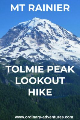The Tolmie Peak Lookout hike has epic views of Mt Rainier. Here it is filling the frame against a clear blue sky with forested hillsides in the foreground. Text reads: Mt Rainer Tolmie peak lookout hike