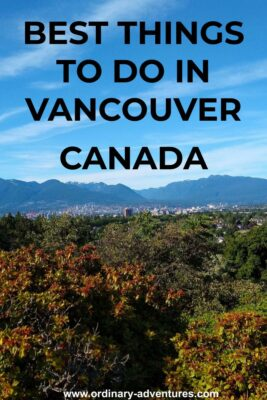 Trees in the foreground and city buildings in the background with forested hills and mountains in the distance. Text reads Best things to do in Vancouver Canada