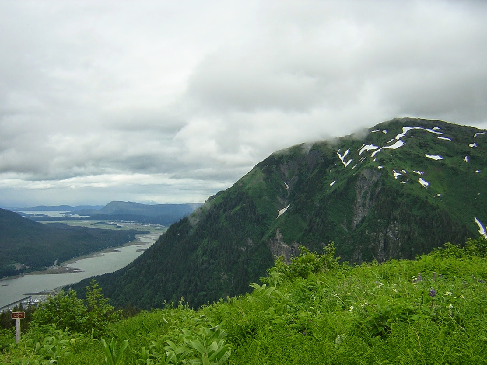 A channel of water between two mountains. There are more mountains in the distance. In the foreground is a green meadow looking down on the water and town below