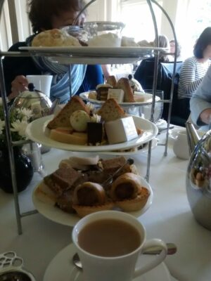A tiered stand with pastries and small sandwiches in a restaurant on a white tablecloth. a cup of tea with milk in a white china cup in the foreground.