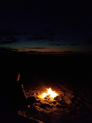 A beach fire after sunset. A person is sitting next to the fire and barely visible. A bit of sunset color remains in the sky.