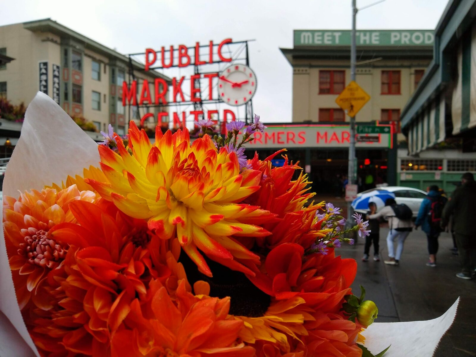 "A bright bouquet of orange, red and yellow flowers is held up in the foreground. In the background is Seattle's Pike Place Market, with a large red neon sign saying ""Public Market Center"" with a red and white clock. There are other buildings and people in the background, slightly out of focus"
