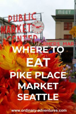 "A bright bouquet of orange, red and yellow flowers is held up in the foreground. In the background is Seattle's Pike Place Market, with a large red neon sign saying ""Public Market Center"" with a red and white clock. There are other buildings and people in the background, slightly out of focus. Text reads: Where to eat at Pike Place Market Seattle"
