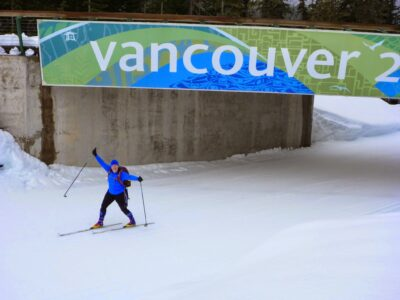 """A person skis under a sign that says """"Vancouver"""" leftover from the Winter Olympics in 2010. Cross country skiing is one winter sport you can learn at Whistler Olympic Park."""