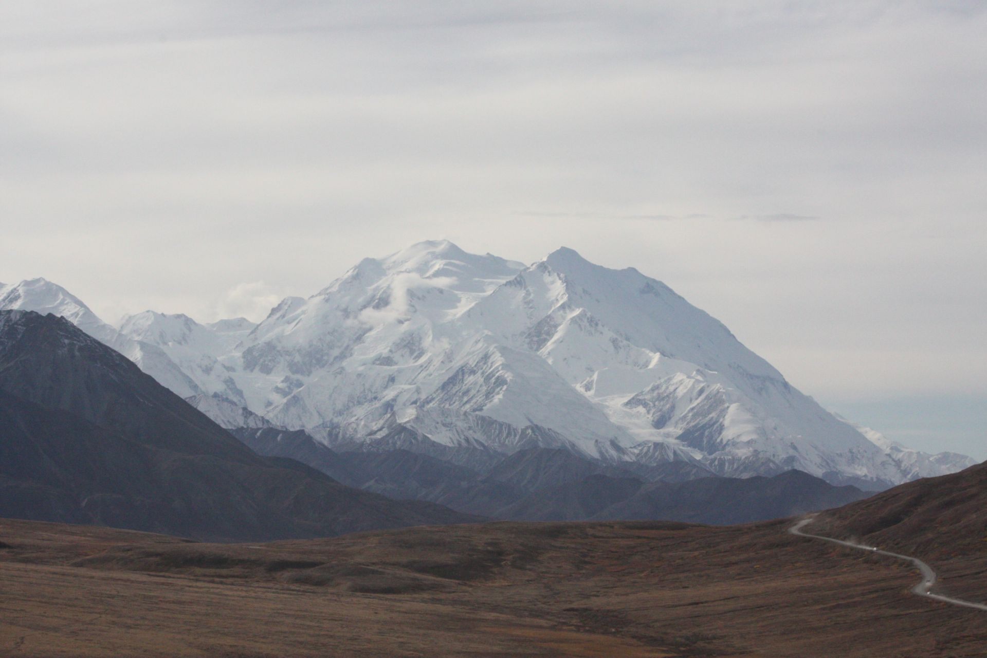 Denali, the highest mountain in North America, rises above a valley and the park road in Denali National Park