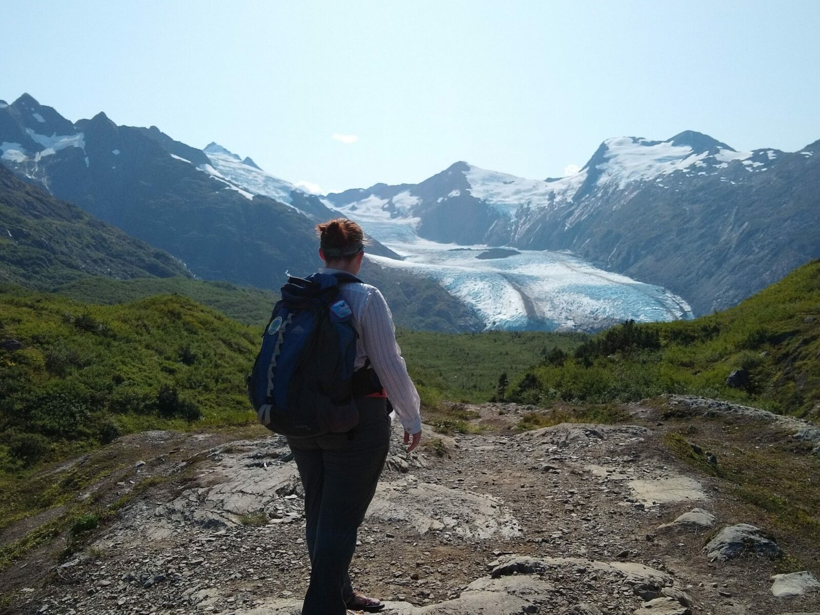Portage Glacier in the distance from Portage Pass. A hiker stands near the trail facing away toward the glacier. It is a sunny day and there are high mountains surrounding the glacier and rocks and green shrubs surrounding the hiker