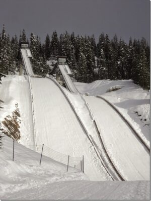 Two very high ski jumps covered in snow are surrounded by forest at Whistler olympic park.