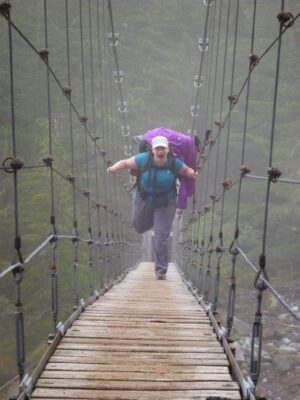 A hiker being goofy wearing a large backpack with purple rain gear tied to it, crossing a wooden suspension bridge in the fog on the mother mountain loop backpacking trip