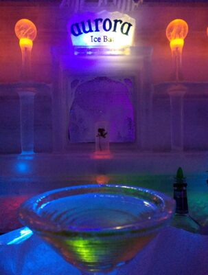 A martini glass made of ice on an ice bar in an ice building. The building is dim with some colored lights offering a bit of light. A sign above the bar reads Aurora Ice Bar