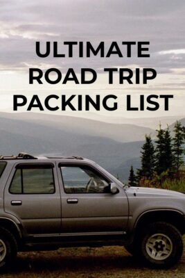 An ultimate road trip packing list includes what you need for your car. An older, silver SUV on a hill with trees above a distant river valley on a cloudy day