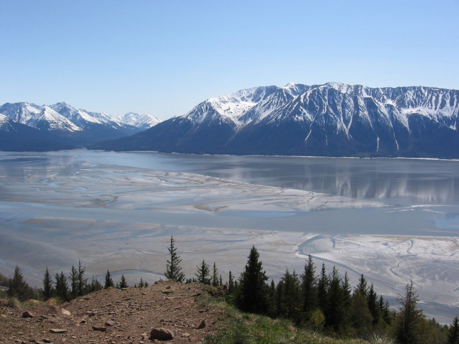 Hiking is one of the best things to do in Anchorage and the Bird Ridge Trail is a tough but spectacular view hike with this view of tideflats, water and across the water mountains with some snow on top