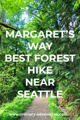 A dirt trail goes through a forest with many shades of green in the trees and undergrowth. Text reads: Margaret's Way, best forest hike near seattle