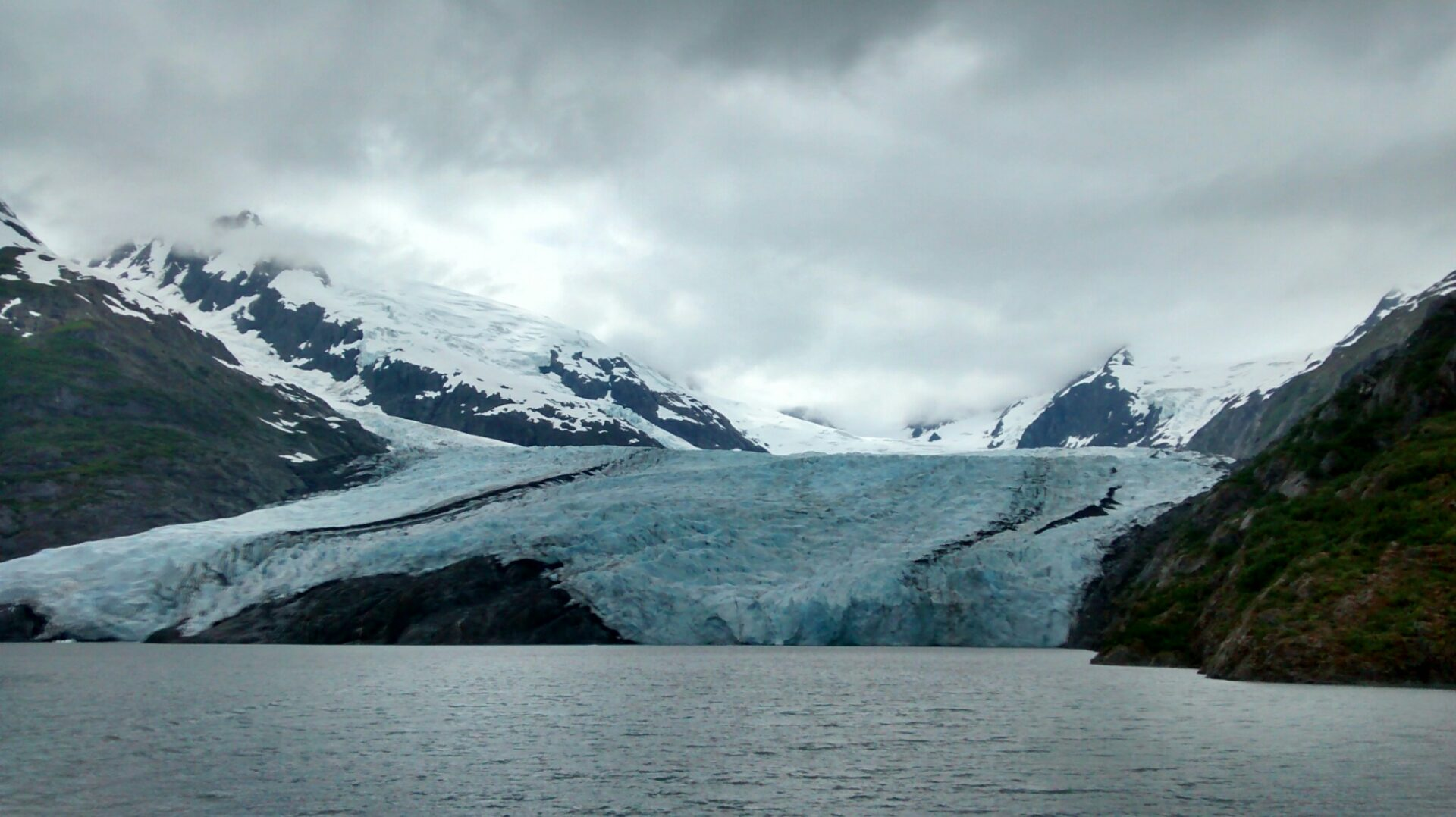 A glacier touches a lake on a cloudy day. There are rocks next to the glacier and mountains and snow in the background