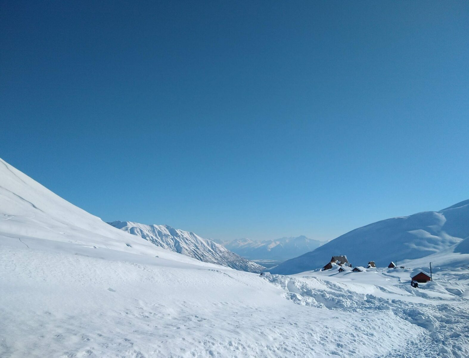 A field of deep snow in a valley with a few cabins. In the distance are more mountains and even more mountains behind that on a blue sky day