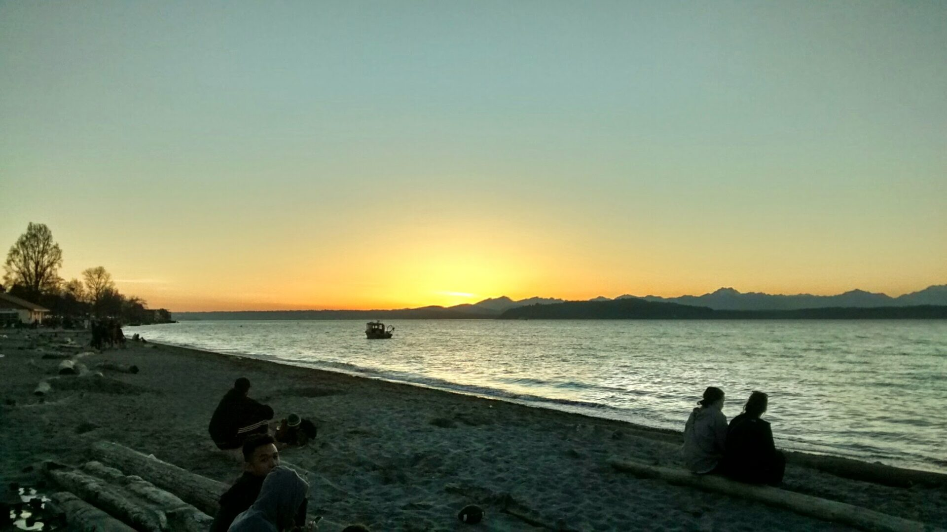 Sunset behind the mountains at a Washington beach, Alki Beach in Seattle. It is getting dark and there are people sitting on logs on the beach, watching the sunset. There is a boat in the water