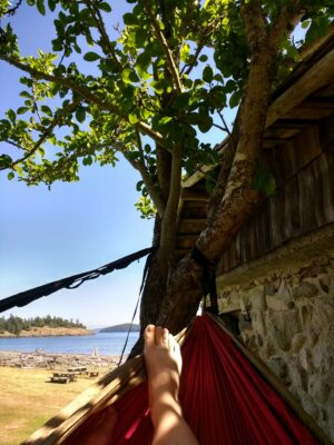 A person's foot is in a hammock in the shade near a Washington beach, spencer spit on Lopez Island