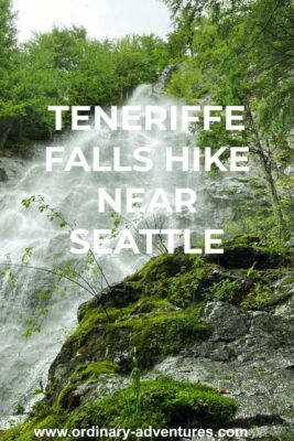 Looking up from the base of a steep waterfall with water and spray coming down a steep rock face. There are rocks and trees surrounding it. Text reads: Teneriffe Falls hike near Seattle