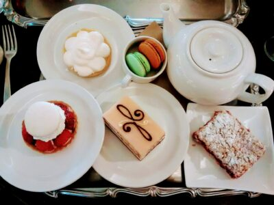 A white teapot and four white plates are on a silver tray. Each plate has a pastry on it and there is a small bowl with two macarons at Murchie's, an excellent alternative to traditional afternoon tea in Victoria BC