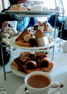 A traditional tea tray at afternoon tea in Victoria, BC. The tray has three white tiers, each with sandwiches and pastries. There is a cup of tea on a saucer next to the tea tray