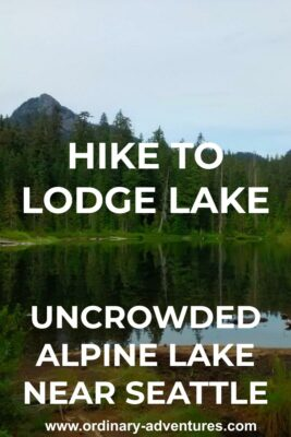 An alpine lake surrounded by evergreen trees. There are a couple of higher mountains visible in the distance. Text reads: hike to Lodge Lake uncrowded alpine lake near Seattle