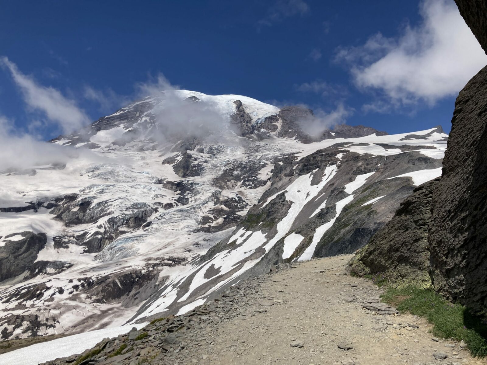 Tahoma or Mt Rainier seen from the Skyline Trail. There is a trail in the foreground and the ice and snow covered mountain rises behind with a few wispy clouds around it on an otherwise clear day. Mt Rainier is a great addition to any seattle itinerary