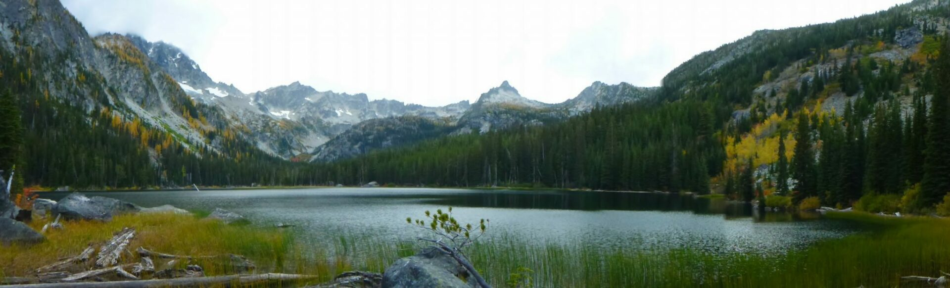 Lake Stuart surrounded by grasses, evergreen trees, golden larches and high distant mountains