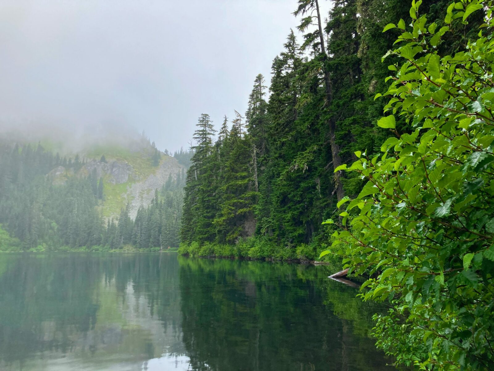 Mirror Lake on a cloudy day is ringed by evergreen trees and mountains which area hidden behind the clouds