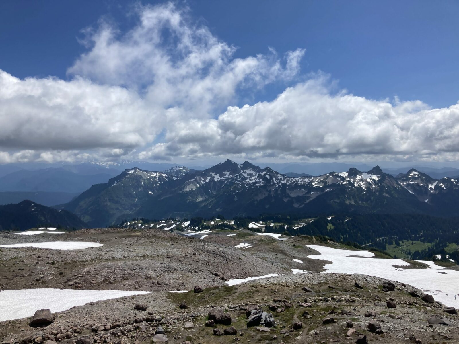 In the foreground, a volcanic landscape of brown rocks and a bit of late season snow along the Skyline Trail. In the background are a range of mountains with some snow still holding on. There are broken clouds against a blue sky.