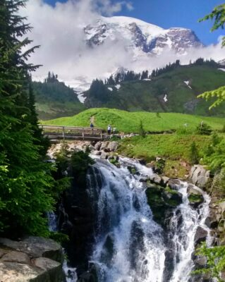 A waterfall with a bridge over it and a few people on a hiking trail. In the background is Mt Rainier, and a few clouds surround it. There are trees and a green meadow beside the trail and waterfall.