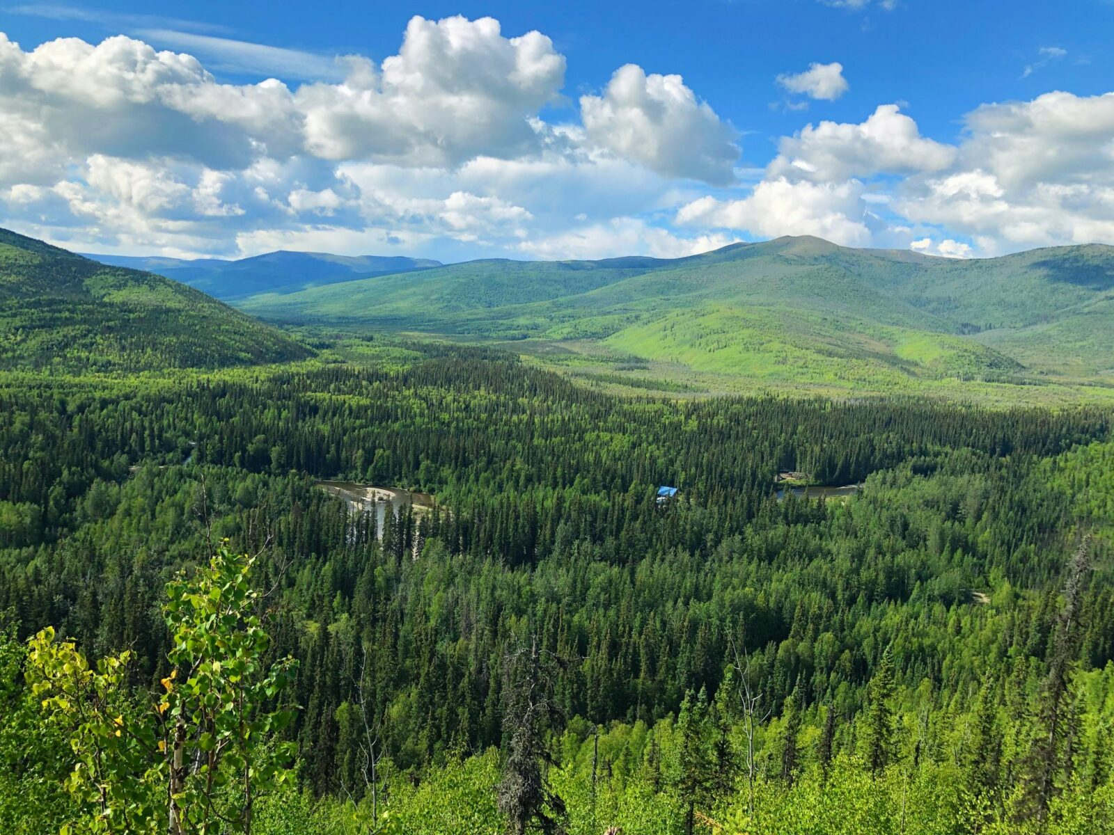 View of forested hillsides and a river below on a partly cloudy day from the angel rocks trail