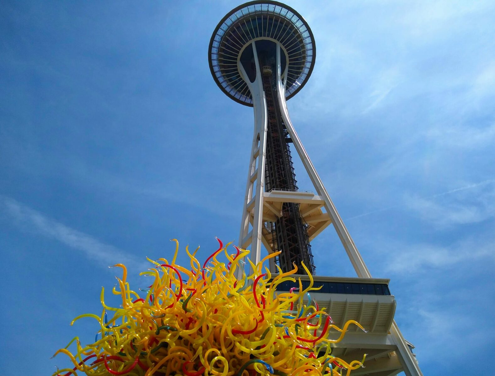 The Space Needle against the blue sky with a yellow glass sculpture in the foreground, an important part of any seattle itinerary