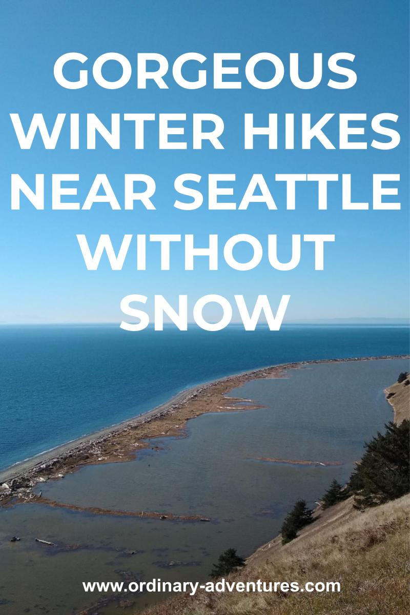 A spit of sand sticks out into a deep blue body of water seen from a cliff above it on a sunny day. Text reads: Winter hikes near Seattle without snow