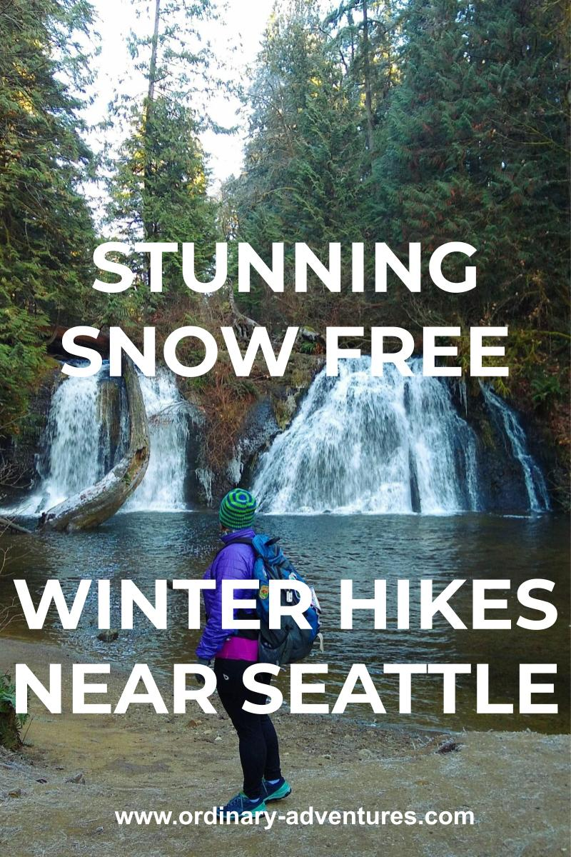 A multi tiered waterfall falls over a low cliff into a pond. There are evergreen trees around it on a cloudy day. In the foreground, a hiker wearing a coat, hat and backpack looks at the waterfall. Text reads: Stunning snow free winter hikes near seattle