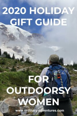 A woman faces Mt Rainier which is partly surrounded by clouds. She has a backpack and a GPS attached to it. Text reads: 2020 Holiday gift guide for outdoorsy women