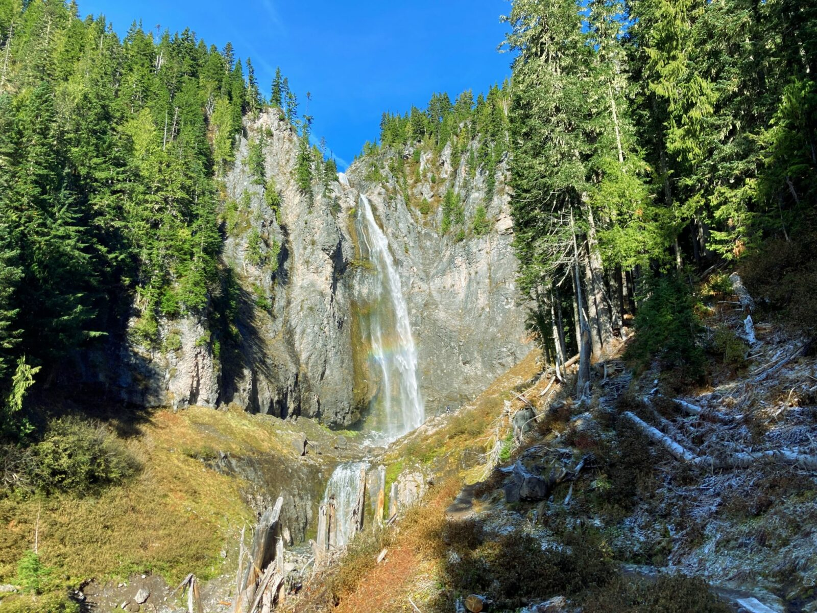 Comet Falls comes straight down a cliff face with forests around the cliff on a sunny day