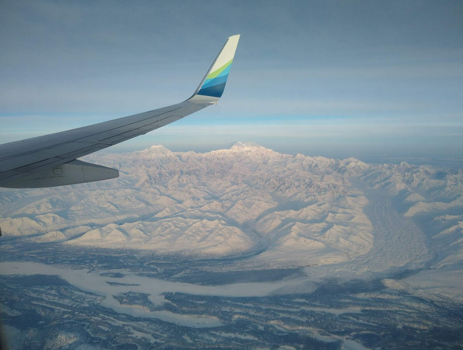 An airplane wing with Denali, glacier, other mountains and the Susitna River below, flying over Alaska in winter