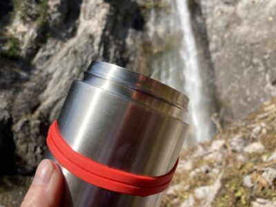 A stainless steel food container being held up in front of a waterfall