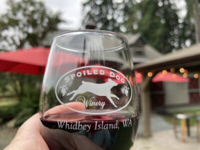 A close up of a glass of red wine. The wine glass has a picture of a dog and says Spoiled dog winery, Whidbey Island WA. In the background are out of focus tables, red umbrellas and outdoor lights.