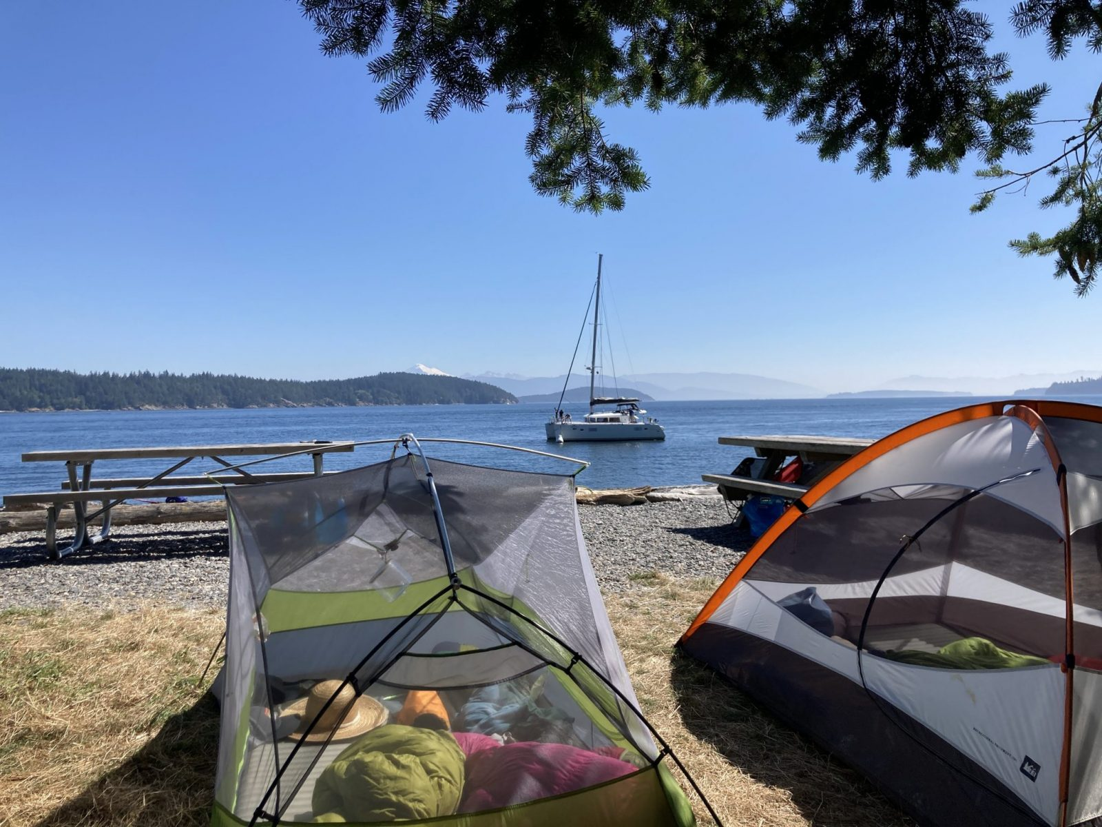 Camping in the San Juan Islands at Pelican Beach. There are two tents with their rain flies off to catch the sun. There are picnic tables and a rocky beach in background. A sailboat is anchored just off shore. In the distance are forested islands and a high snow covered mountain.