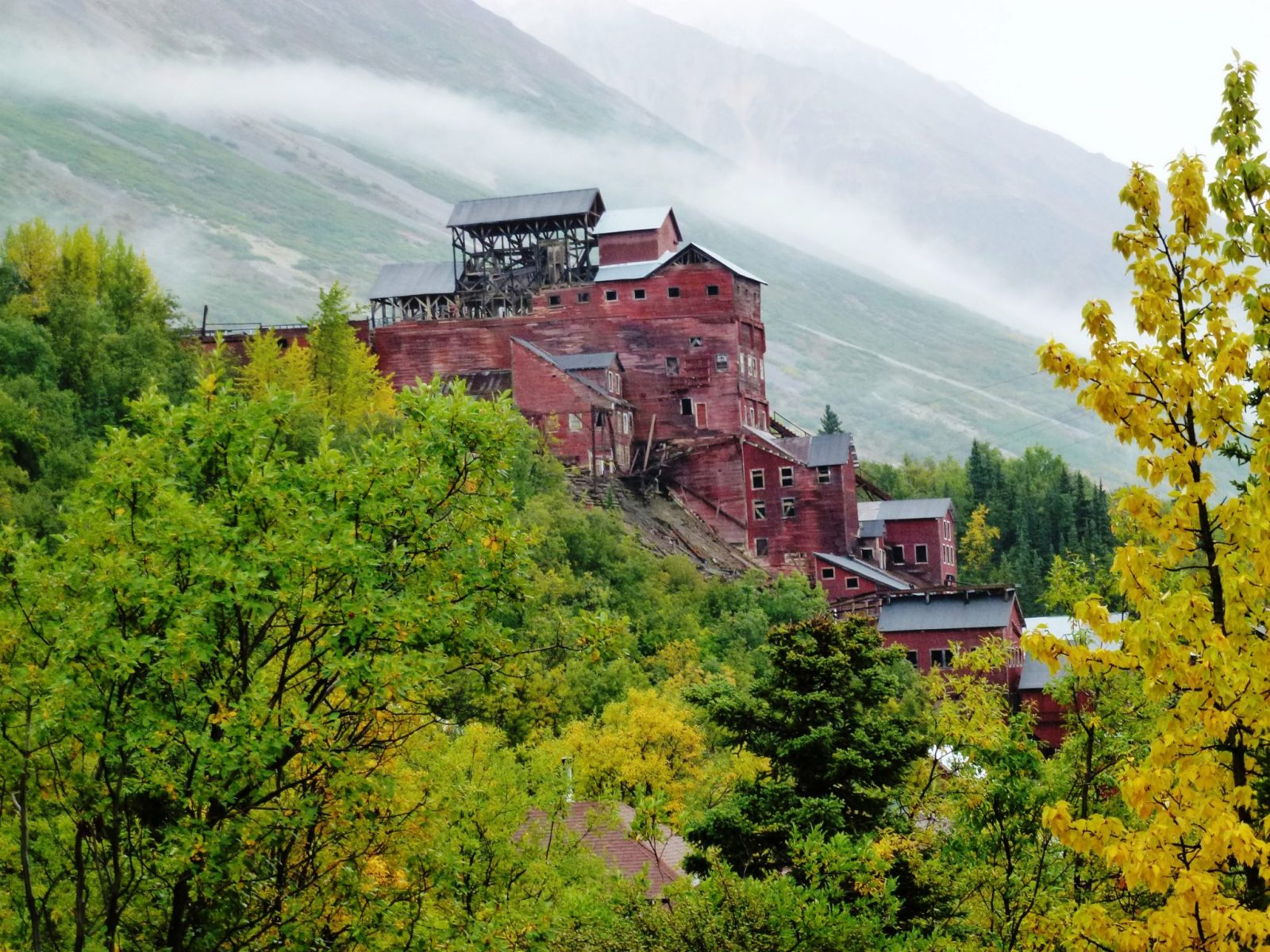 A ruined large wooden structure, the historic Kennicott mine is built into a hillside. The building is painted red with a black roof. There are trees in the foreground and a mountain in the background in Wrangell-St Elias National Park in Alaska