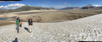 Three hikers walk up a snow field with a volcanic landscape in the background covered in pumice. There are mountains in the distance in the valley of 10,000 smokes in Katmai national park in alaska