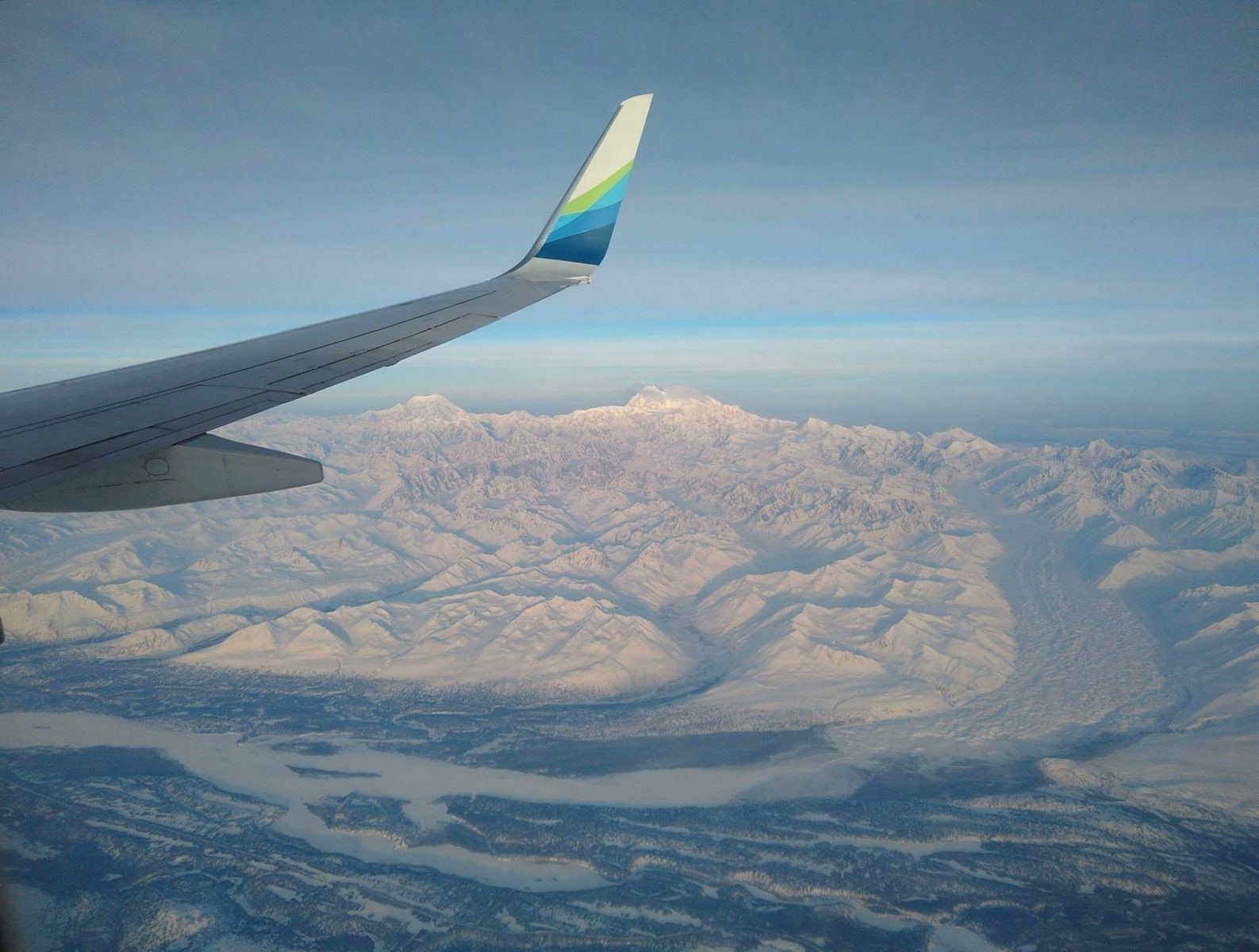 Denali National Park below the wing of an airplane. There are mountains, glaciers and a river valley
