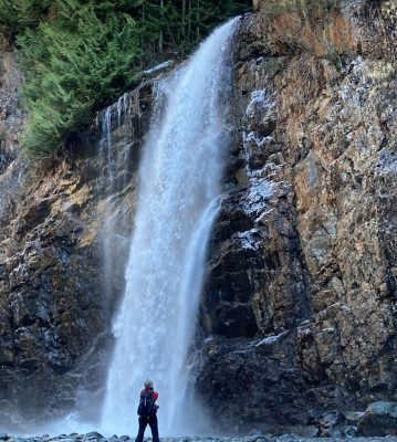 Franklin Falls in winter with only a bit of ice and snow around it. The waterfall is plunging over a vertical cliff. A hiker is taking a photo of the waterfall wearing a wool hat and a red jacket