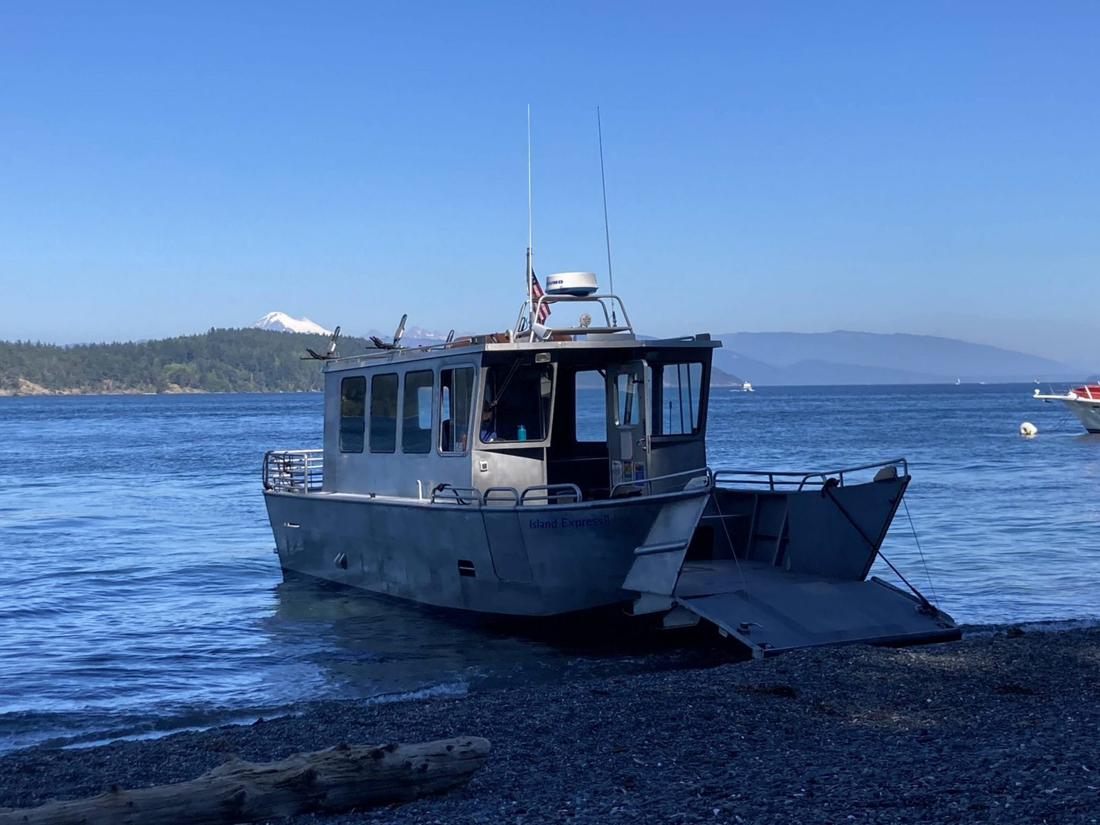 A metal charter boat is beached with it's ramp down to let hikers disembark. It's a gravel beach in the San Juan Islands with forested hillsides and a high mountain in the distance