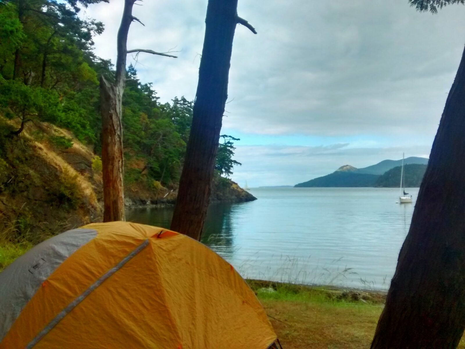 Camping in the San Juan Islands on Jones Island. An orange and white tent is between a few trees near the beach. There are green trees along the shore and a sailboat anchored in the bay. In the distance are more forested islands